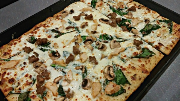 Chuck E. Cheese's specialty pizza Cali Alfredo (includes spinach, creamy alfredo sauce, sausage, mushrooms and chicken).